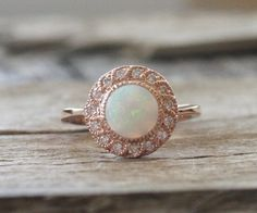Handmade 14K rose gold hand milgrain diamond halo ring featuring a natural white Australian fiery opal measuring 7 mm and weighing 0.75 ct. (VS)