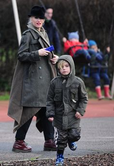 Action man: Kingston runs off looking like a mini soldier in a khaki rain coat and camouflage trousers