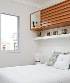 Quarto de casal pequeno com armário em cima da cama