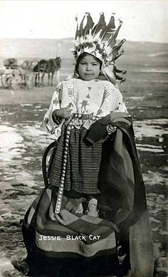 Young girl Jesse Black Cat in beaded top, concho belt, and war bonnet with trailer. Pine Ridge 1900. Strong young girl!