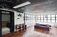 Outstanding concept; Stunning hardwood floors, vintage auditorium chairs, prop-out windows and chalkboard ceiling. Cinder-block table? Uh, pass.