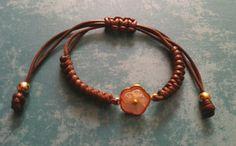 Pulsera ajustable cordón marrón y accesorios de acero dorado. S/.36.00