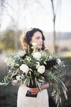 Leafy green and white centerpiece pops of black and feathers