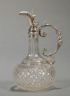 Russian Silver-mounted Colorless Cut Glass Claret Jug, 1908-17, bearing maker's mark for Julius Alexandrovitch Rappoport, and with Faberge mark, the ovoid body cut with diamonds centered by cruciforms, with slender, paneled neck mounted with beaded silver bands with short spout, the small lid with beaded finial, and with fish scale-patterned C-scroll handle.