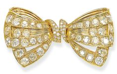 A GOLD AND DIAMOND DOUBLE CLIP BROOCH, BY BOUCHERON  Designed as an articulated fluted gold bow, set with old-cut diamonds, to the pavé-set central knot, mounted in 18k gold, 7.8 cm long Signed Boucheron