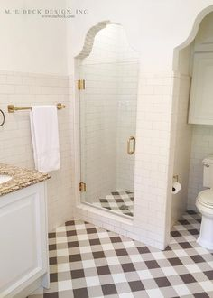 White and brown bathroom features white subway tiles that dominate most of the walls lined with a brass towel bar alongside white and brown buffalo check pattern tile floor. A walk in shower is clad in white subway tiles on walls and white and brown plaid tiles on shower floor placed next to an alcove filled with a toilet under a cabinet.