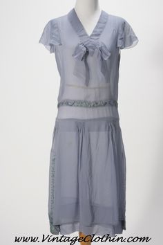 This 1920s-30s Art Deco Flapper Dress BLUE Sheer Silk Crepe Dress is from our personal collection.    This 1920s-30s flapper dress, is true vintage and in art deco style it's made of sheer silk crepe in a dusty blue color, with drop waist and short, fluted sleeves, as well as a stunning silk ribbon design at the waist and down the sides of the dress. #1920 #1920s #vintage #vintageclothin #flapper #dress #artdeco www.vintageclothin.com