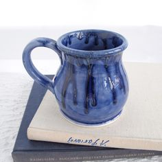 A handmade wheel-thrown round belly earthenware mug, finished with a hand pulled handle by Marietta. Glazed with her Frothy light sea blue bright glaze, with blue silver highlights. (Microwave, dishwa