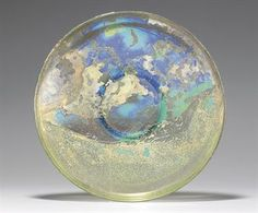 A ROMAN GLASS PLATE CIRCA CENTURY A. Transparent green in color, free-blown, of broad, shallow form on an applied ring foot, with a thin groove on the exterior of the rim; extensive iridescence throughout in. Ancient Rome, Ancient History, Forma Circular, Roman Art, Arte Popular, Glass Ceramic, Ancient Artifacts, Ancient Civilizations, Antique Glass