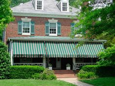 Green and burgundy awnings on the porch of a two-story red brick house with green shutters. Cottage Shutters, Green Shutters, Building Exterior, Brick Building, Canvas Awnings, Aluminum Awnings, Porch Awning, Shutter Colors, Courtyard Pool