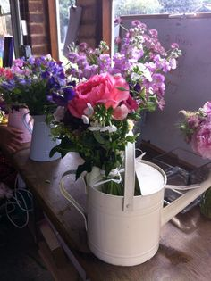 Enamel jugs and watering can filled with country flowers