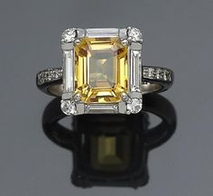 A yellow sapphire and #diamond ring centering a radiant-cut yellow sapphire, weighing approximately: 3.00 carats; mounted in eighteen carat white gold. http://www.jangmijewelry.com/