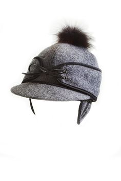 It's the chicest winter cap on the block. Made with a cozy, warm wool blended outer layer, this Railroad Cap features a quilted lining and leather lace-up tie detail, topped off with a vintage fur pompom. Wear it with the ear flap invisibly tucked up or untuck it for extra ear warmth.    Size: Medium-Large (7 3/8)   Railroad Cap by Headmistress. Accessories - Hats Canada