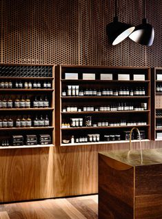 Aesop Emporium Melbourne by .PSLAB.  A scooped-out surface in the top of an island makes way for a curving copper trough for a wash basin and two slim copper taps are attached to the exterior of the box.