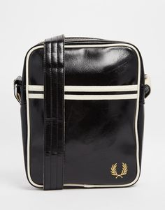 """Flight bag by Fred Perry Shiny leather-look fabric Zip top closure Piped trims Adjustable shoulder strap Inner zipped pocket Wipe clean 100% Polyvinylchloride H: 27cm/ 11"""" W: 21cm/ 8"""" D: 5cm/ 2"""""""