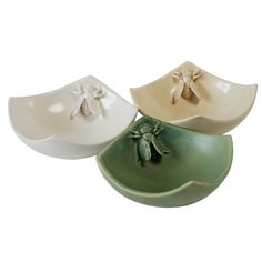 adorable, small celadon ceramic bowls with little bees perched near the tops