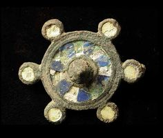 8144. ROMANO BRITISH INLAID BROOCH, c. 3rd-4th century AD. The brooch of circular form with 6 small circles on the perimeter, all inlaid with blue, white and yellow enamels. Pin missing as usual. 1.3 inches. Much of enamel remaining. Rare.  On sale at: $1250.  Antiquity Merchant
