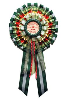 Rosette crafted by Cathe Holden from vintage shelf edging paper, ribbon, suspenders and a milk cap.