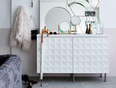 Armário para entrada feito com dois armários de cozinha brancos com portas com textura e pés em aço inoxidável