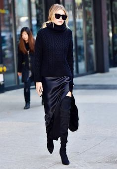 Gigi Hadid wears a cable-knit turtleneck sweater, high-slit silk skirt, thigh-high boots, and black accessories