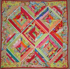 The thin white sashing makes each block pop.  Good idea for a busy quilt.
