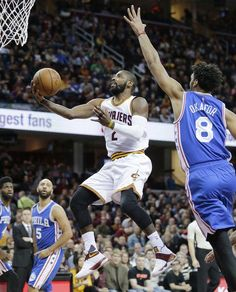 The Cavaliers' Kyrie Irving drives to the basket against the Philadelphia 76ers' Jahlil Okafor during the first half of Sunday in Cleveland.