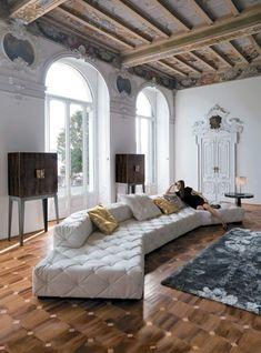 Antique modern mix living room. Tufted couch, high ceilings with exposed beams, and vintage interior design details.