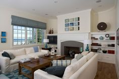 A soothing neutral color palette brings a light and airy feel to this lakefront living room. Soft blue accents found in the pillows, rug and artwork match the stunning lake views beyond.