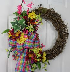 * Part of our Budget Friendly Collection  This happy and funky grapevine wreath has a brightly colored check bow, and colorful large flowers that have the wild colors to match!  Hot pink dogwoods, yellow daisies, lime green freesias are included in this wreath pulling from the bright colors in the bow AND those matching funky flowers! Variegated ivy is added throughout.  This wreath can take you from spring through summer for your door décor ~ OR ~ it could be fun on an inside wall! Back of…
