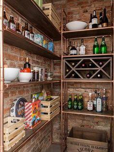Despensa organizada con librerías de tubos de cobre y ladrillo visto