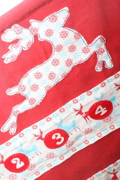Red Reindeer advent calendar Close up on embroidered detail.