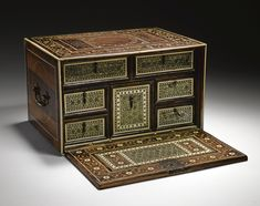 A FINE IVORY-INLAID SADELI CABINET, INDIA, GUJARAT, 17TH CENTURY of rectangular form with hinged drop front revealing seven panels with six drawers each with drop handles, decorated with sadeli panels bordered by narrow bands of ivory and stained wood, brass loop handles to sides, the top and front inlaid with ivory floral scrolls and roundels, quatrefoil lock-plate and key