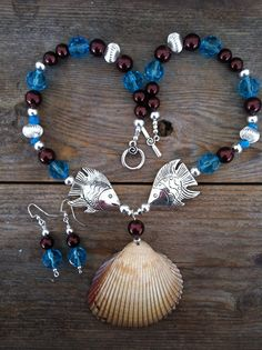 The mixture of sea blue and chocolate brown glass beads on this necklace set enhance the natural beauty of the shell pendant. SOLD