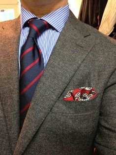 Dark grey jacket, white shirt with blue candy stripes, navy tie with red stripes