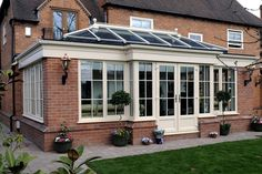 Cream UPVC brick built orangery with astragal bar and cornice gutter and french doors