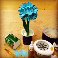 Chrysanthemum made from paper flowers glued to a styrofoam ball, stuck on an old plastic crayon holder, set in plaster in a yogurt container.  #artprojectsforkids #recycledart