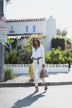 """ Go all out this September and give the all-white look a try! Aimee Song demonstrates just how glamorous this style can be, pairing distressed white jeans with a plunging V neck top. Bring this look together with a leather belt to..."