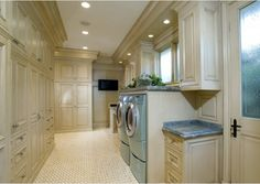 This grand laundry room is magnificent!  The custom antiqued cabinets provide plenty of extra storage – so organized and beautiful.