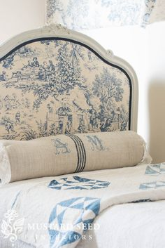 Reupholstering the antique French daybed with blue toile fabric - this is Festin in Bleu by Stof with a navy braided gimp trim. This upholstered daybed with a padded frame lets the sewing room double as a guest bedroom. The painted wood frame and DIY upholstered panels are just like upholstering a bedroom headboard and footboard. Find a link with photo tutorial, suggested supplies, and before & after photos! - Miss Mustard Seed #missmustardseed #daybed #reupholstery #upholstery #guestbed…