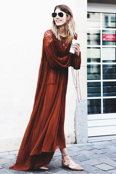 Veronika Heilbrunner wears a rust colored maxi dress with lace paneling, lace-up flats, and aviator sunglasses