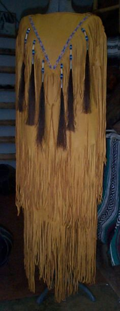 Gold deer hide dress horse hair tassels, bone hair pipe, glass beads and lazy stitch beadwork on V, lots of fringe that is all hand sewn and stitched. http://nativeamericanstuff.net/Native%20American%20Style%20Crafted%20Clothing%20buckskins%20outfits%20moccasins%20and%20Handbags.htm