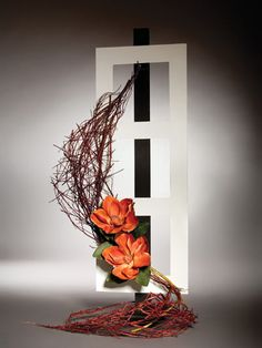Framed Flair This modern art piece was constructed using fresh red dogwood twigs that were twisted and wired to form a graceful curve of dried material. A white foam board frame provides the background onto which rich autumn-coloured magnolias were added to complete this design and provide a pop of colour.