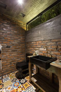 This pool house bathroom features brick walls and exposed concrete, while the floor is covered in colorful patterned tiles.
