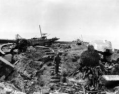 A la pointe du Hoc après les bombardements, un GI dans les ruines d'un encuvement d'un canon de 155 mm visible à gauche.
