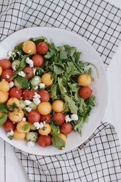 a summer melon salad with arugula, watermelon, cantaloupe, goat cheese, and a honey-lime dressing