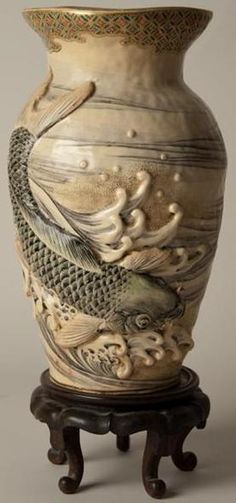 A JAPANESE SATSUMA PORCELAIN VASE, OVOID HAVING A FLARED RIM, WAVES AND CARP FIGURES IN DEEP RELIEF, FITTED MAHIGANY STAND. CIRCA 1801-1900