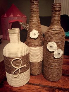 Upcycled wine bottle project - twine wrapped with macramé rope initial and flower accents.