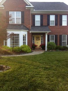 Everything from the monogrammed decoration on the yellow door with the dark brick and black shutters not to mention the front porch flowers! #homey #perfection