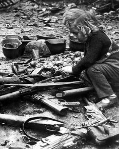 A child plays with guns left in the streets of Berlin, 1945.