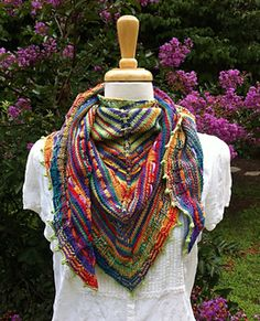 """This basic shawl pattern looks anything but """"basic"""" when knitted with alternating colors of yarn. Eyelet rows are added so you can weave ribbons through the stitches to add decoration and variety to the shawl. A wide ribbed """"ruffle"""" and picot bind off finishes it off with pizzazz! You can choose two solid color yarns, or one solid and one variegated, or two variegated. This shawl is sure to let the colors sing!"""